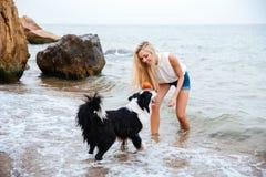 Nette Frau, die mit Hund auf der Küste spielt Lizenzfreie Stockbilder