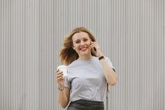 Nette Frau, die mit ihrem Telefon beim Trinken des Kaffees spricht Stockfotografie