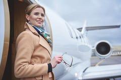 Nette Frau, die nahes Flugzeug steht stockfotos