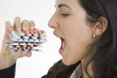 Nette Frau, die Pillen isst Stockbild
