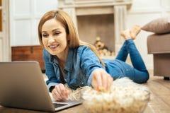 Nette Frau, die Popcorn auf dem Boden isst Stockfoto