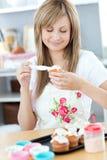 Nette Frau, die Sahne auf kleine Kuchen setzt Lizenzfreie Stockfotos