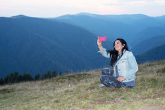 Nette Frau, die selfie in den Bergen tut Stockfoto