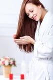 Nette Frau, die um ihrem Haar sich kümmert Lizenzfreies Stockfoto