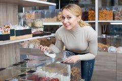 Nette Frau, die verschiedene kandierte Früchte vorwählt Stockfoto