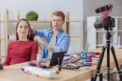 Nette Frau, die zur Kamera während ihre Friseurfunktion lächelt Stockbilder