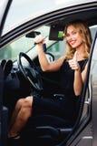 Nette Frau im Auto, Schlüssel halten und zeigen Daumen Lizenzfreies Stockbild
