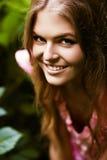 Nette Frau im grünen Busch Stockfoto