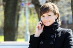 Nette Frau im Park mit Mobiltelefon Stockfotografie