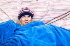 Nette Frau im Winterhut eingewickelt im Duvet lizenzfreie stockfotografie