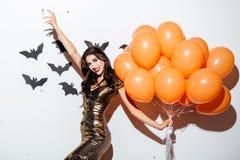 Nette Frau mit dem Vampirsmake-up und orange Ballonen, die Spaß haben Lizenzfreies Stockfoto