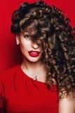 Nette Frau mit den roten Lippen im roten Kleid mit Locken Lizenzfreies Stockfoto