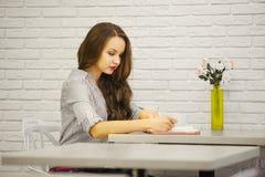 Nette Frau mit flüssigem Haarschreiben in den Anmerkungen bei Tisch lizenzfreies stockbild