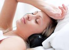 Nette Frau mit Kopfhörern auf dem Lügen auf einem Bett Stockbilder