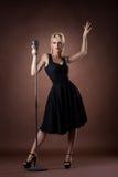 Nette Frau mit Mikrofon auf dunklem Hintergrund Stockfoto
