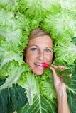 Nette Frau mit Salatblättern vereinbarte um ihren Kopf, der ein r isst Stockbild