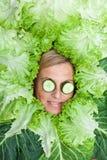 Nette Frau mit Salatblättern vereinbarte um ihren Kopf mit cucum Stockfoto