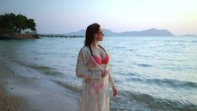 Nette Frau mit Sommersprossen in einem rosa Badeanzug und in einem weißen Kleid in der Sonnenbrille auf einem weißen sandigen Str stock video