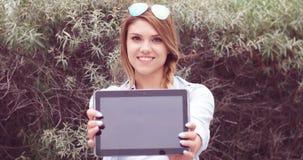 Nette Frau mit Tablet gegen hohe Gräser Stockbilder