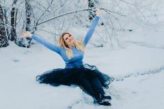Nette Frau sitzt in einem Schneewinter lizenzfreie stockfotos