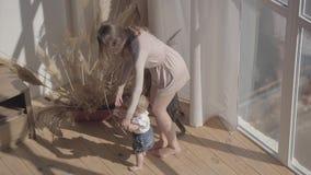 Nette Frau und ihre Babystellung auf dem Boden zu Hause Das Kind, das ersten Schritt, Mutter sie stützen lässt Mutterspiele stock video
