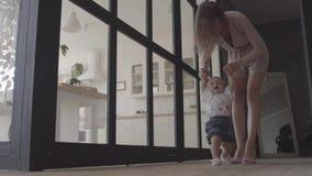 Nette Frau und ihre Babystellung auf dem Boden zu Hause Das Kind, das ersten Schritt, Mutter sie stützen lässt Mutterspiele stock footage