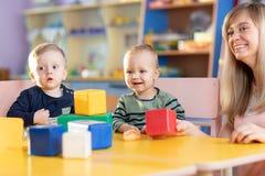 Nette Frau und Kinder, die pädagogische Spielwaren am Kindergarten oder am Kindertagesstättenraum spielen stockbild
