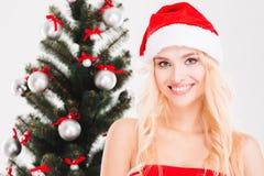 Nette Frau in Weihnachtsmann-Hut, der nahe Weihnachtsbaum aufwirft Lizenzfreies Stockbild