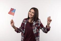 Nette nette Frau, welche die US-Flagge hält Stockbild
