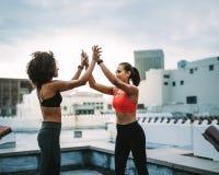 Nette Frauenathleten, die hoch fünf während des Trainings geben lizenzfreie stockfotografie