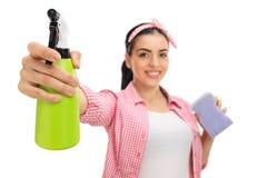Nette Frauenreinigung mit einem Spray und einem Schwamm Stockfoto