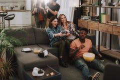 Nette Freunde, die Videospiele, das Plaudern, das Essen und das Trinken spielen stockfotografie