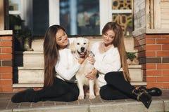 Nette Freunde mit einem Hund draußen Stockbild