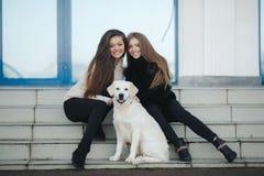 Nette Freunde mit einem Hund draußen Lizenzfreie Stockbilder