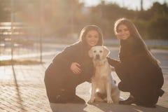 Nette Freunde mit einem Hund draußen Lizenzfreie Stockfotos
