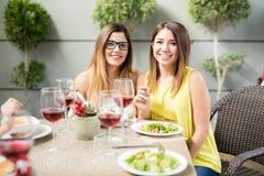 Nette Freundinnen, die heraus essen lizenzfreie stockbilder