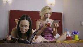 Nette Freundinnen, die Spaß im Bett zu Hause haben stock footage