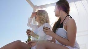 Nette Freundinnen schauen, um zu überholen, Vorhänge auf Bungalow sich entwickeln im Wind, stock video