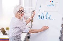 Nette gealterte Geschäftsfrau, die das weiße Brett im Büro verwendet lizenzfreie stockbilder