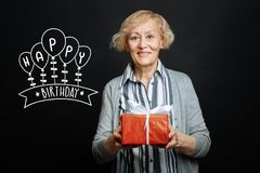 Nette gealterte lächelnde Dame beim Halten eines Geburtstagsgeschenkes lizenzfreie stockfotografie