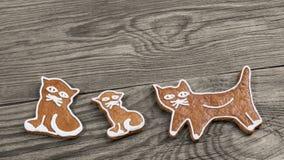 Nette gebackene Lebkuchenbonbons Katzenformen auf hölzernem Hintergrund stockfotografie