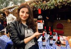 Nette georgische Frau, welche die Flaschen Rotwein, specialy hergestellt für Festival zeigt lizenzfreie stockfotografie