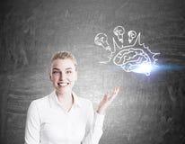 Nette Geschäftsfrau, die Gehirn mit Birnen zeigt Stockfotos