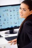 Nette Geschäftsfrau, die vor Computer sitzt Stockbild