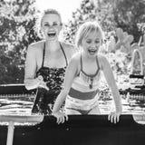 Nette gesunde Mutter und Tochter beim Swimmingpoolspielen Lizenzfreie Stockfotografie