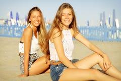 Nette glückliche blonde Jugendliche, die auf dem Strand lächelt sitzen, Kamera schauend Lizenzfreies Stockbild