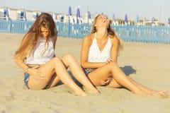 Nette glückliche blonde Jugendliche, die auf dem Strandlachen sitzen Stockfoto