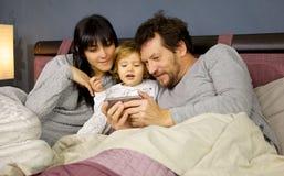 Nette glückliche Familie im Bett mit aufpassendem Video der kleinen Tochter auf mittlerem Schuss des Handys Stockbild