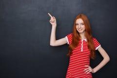 Nette glückliche Frau, die auf copyspace über Tafelhintergrund zeigt Lizenzfreies Stockfoto