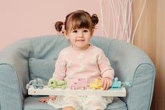 Nette glückliche 2 Jahre alte Baby, die zu Hause mit hölzernen Spielwaren spielen Lizenzfreie Stockfotografie
